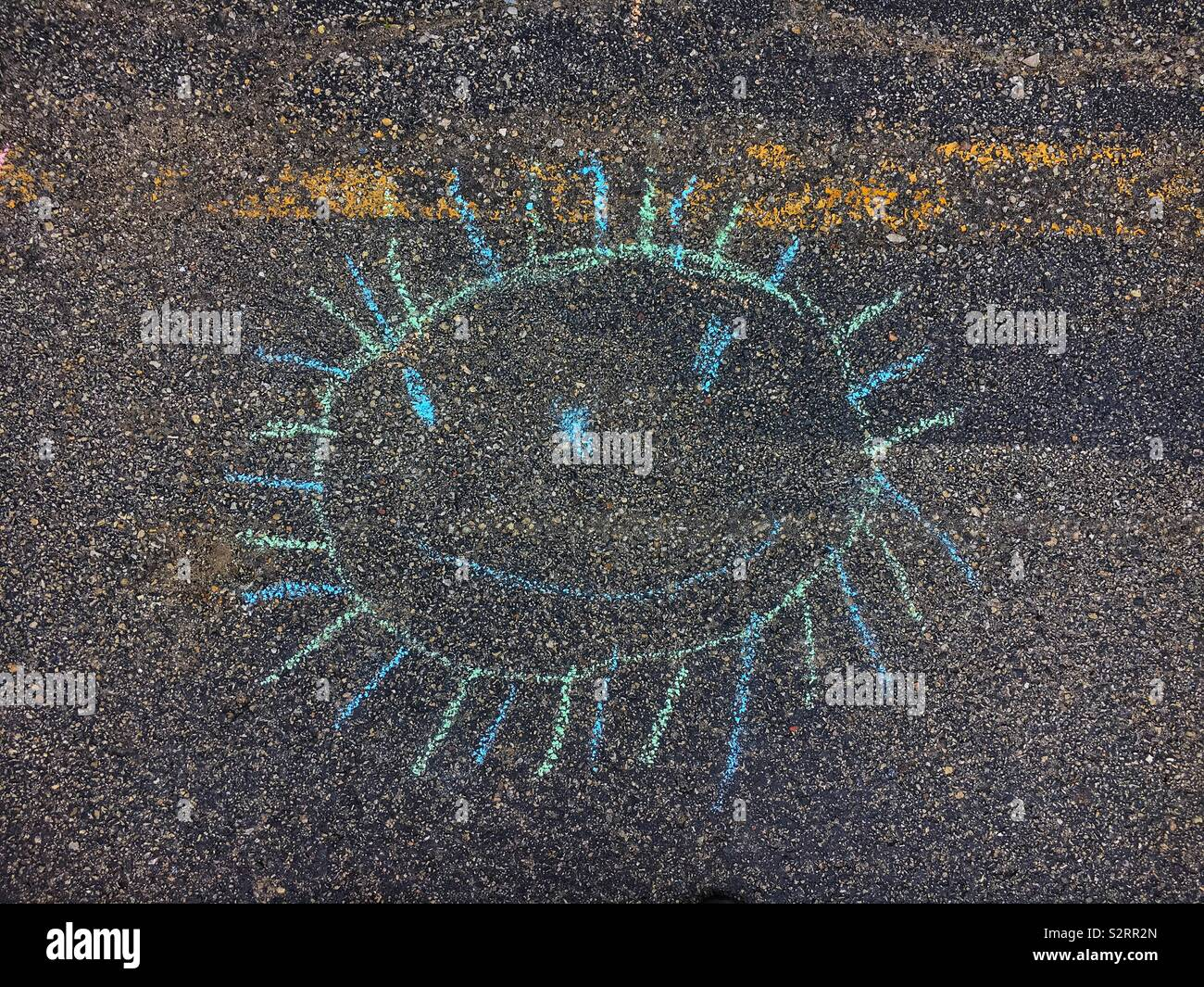 Chalk drawing on pavement of a smiling sun made by a third grader. Stock Photo