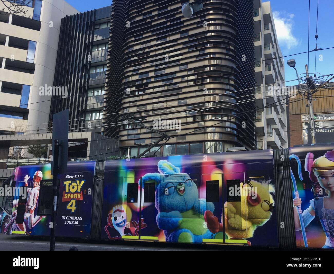 During the Victorian school holidays, a tram displays a vibrant Disney Pixar Toy Story 4 movie advertisement whilst travelling along Commercial Road, South Yarra in the heart of Melbourne City. - Stock Image
