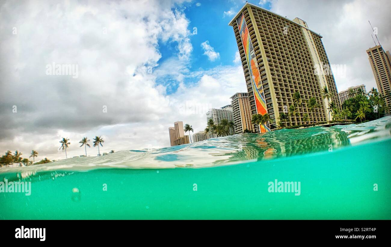 Hilton Hawaiian Village in Waikiki as seen from the ocean with split perspective. - Stock Image