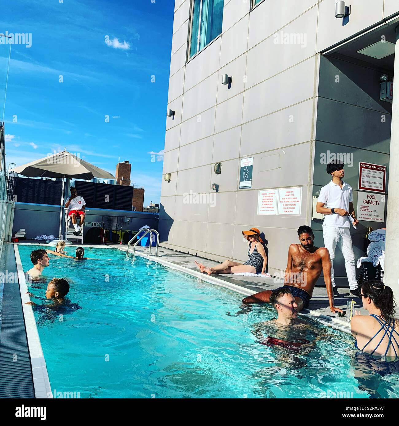 Guests enjoy the pool at the Hotel Indigo Lower East Side, New York City - Stock Image