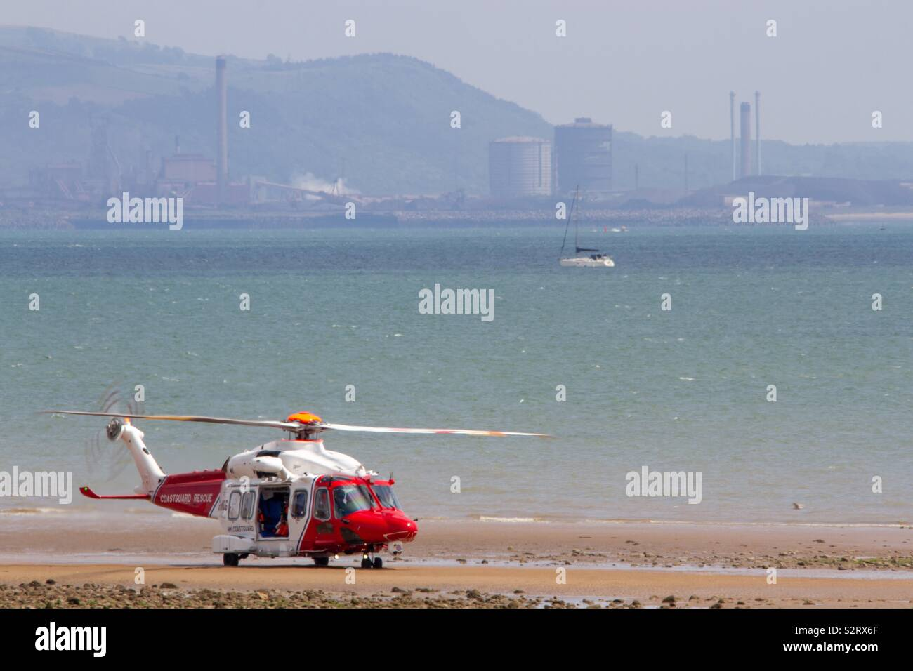 Coast guard landing on beach with an industrial backdrop - Stock Image
