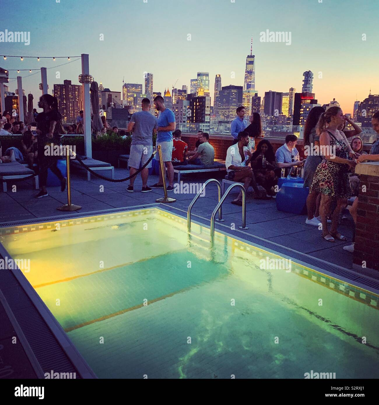 Patrons of the Mr. Purple bar socialize near the pool with the Lower Manhattan skyline in the background at the Hotel Indigo Lower East Side, New York City - Stock Image