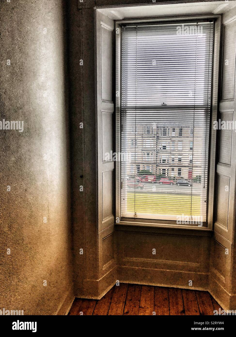 Looking through Venetian blind from empty room - Stock Image