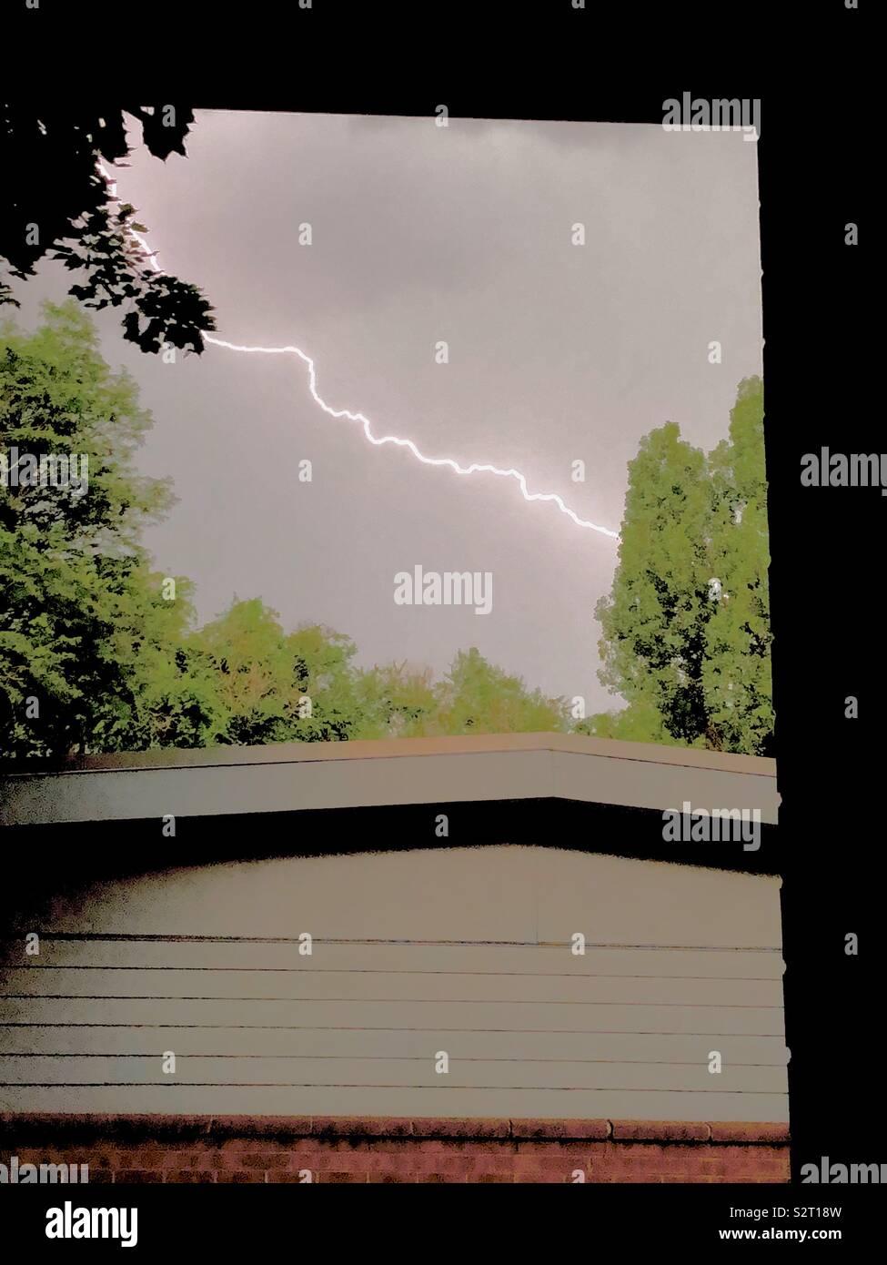 Lighting strike in residential neighborhood- Hand-held, manual capture. - Stock Image