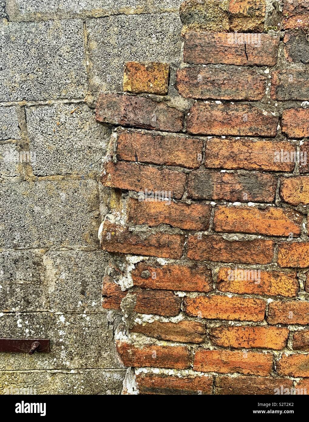 Half demolished brick wall with breeze block wall behind - Stock Image