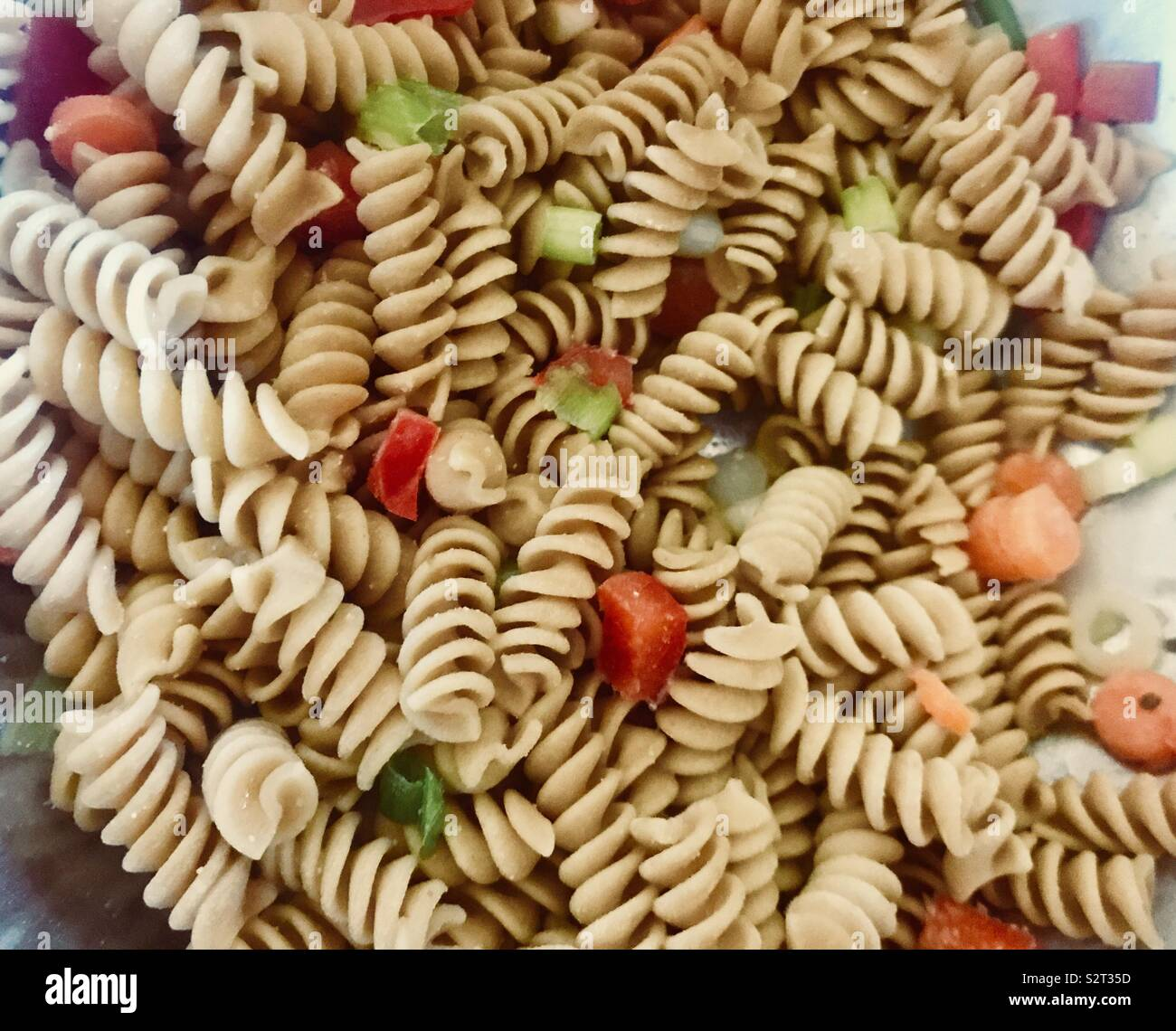 Yummy Pasta salad on a summers afternoon with bell peppers, carrots and salad dressing for seasoning - Stock Image