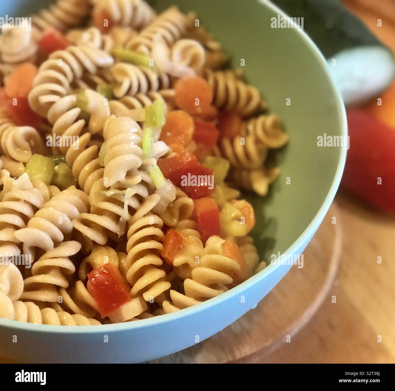 A bowl of pasta salad with bell peppers, cucumbers,carrots and garlic seasoning with the ingredients off to the side of the pasta bowl. - Stock Image