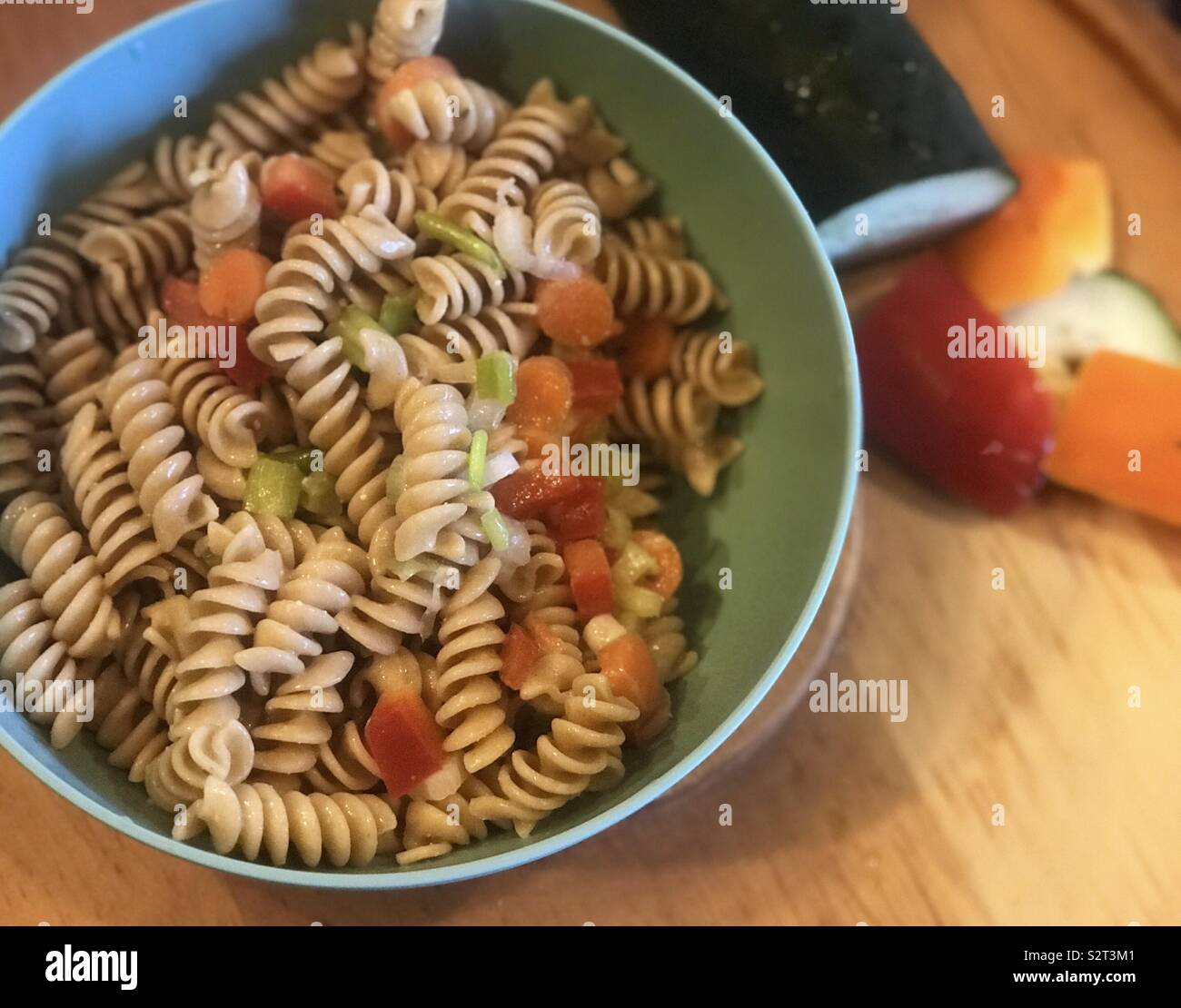 A delicious bowl of pasta salad with bell peppers, cucumbers, garlic seasoning and carrots, with chopped vegetables displayed on the side. - Stock Image
