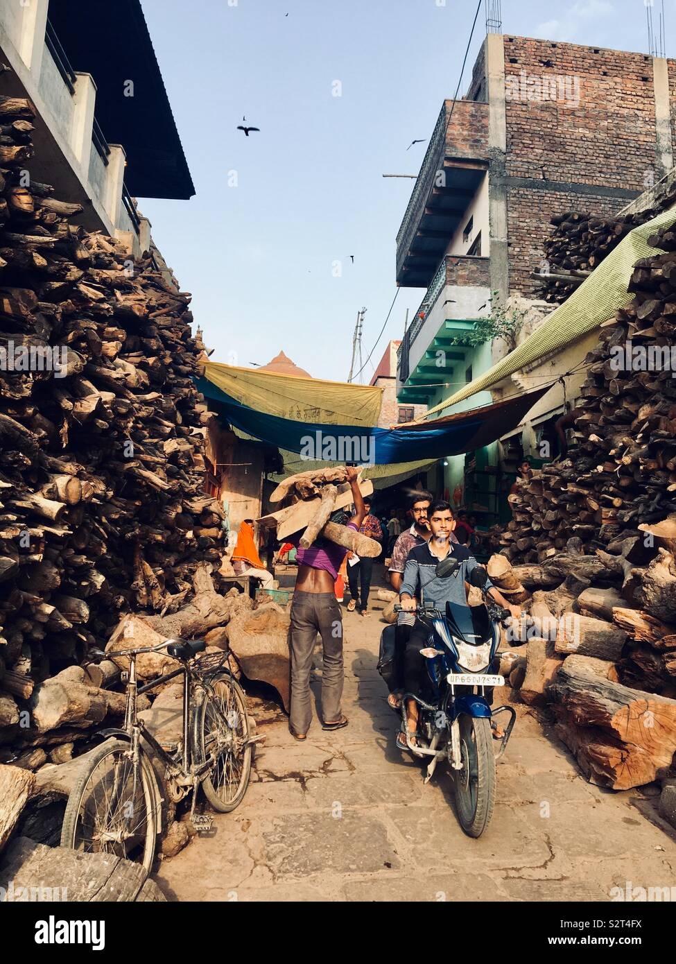 A man walking up an alley carrying the firewood used for the funeral burnings on a hot summer day in Varanasi - Stock Image