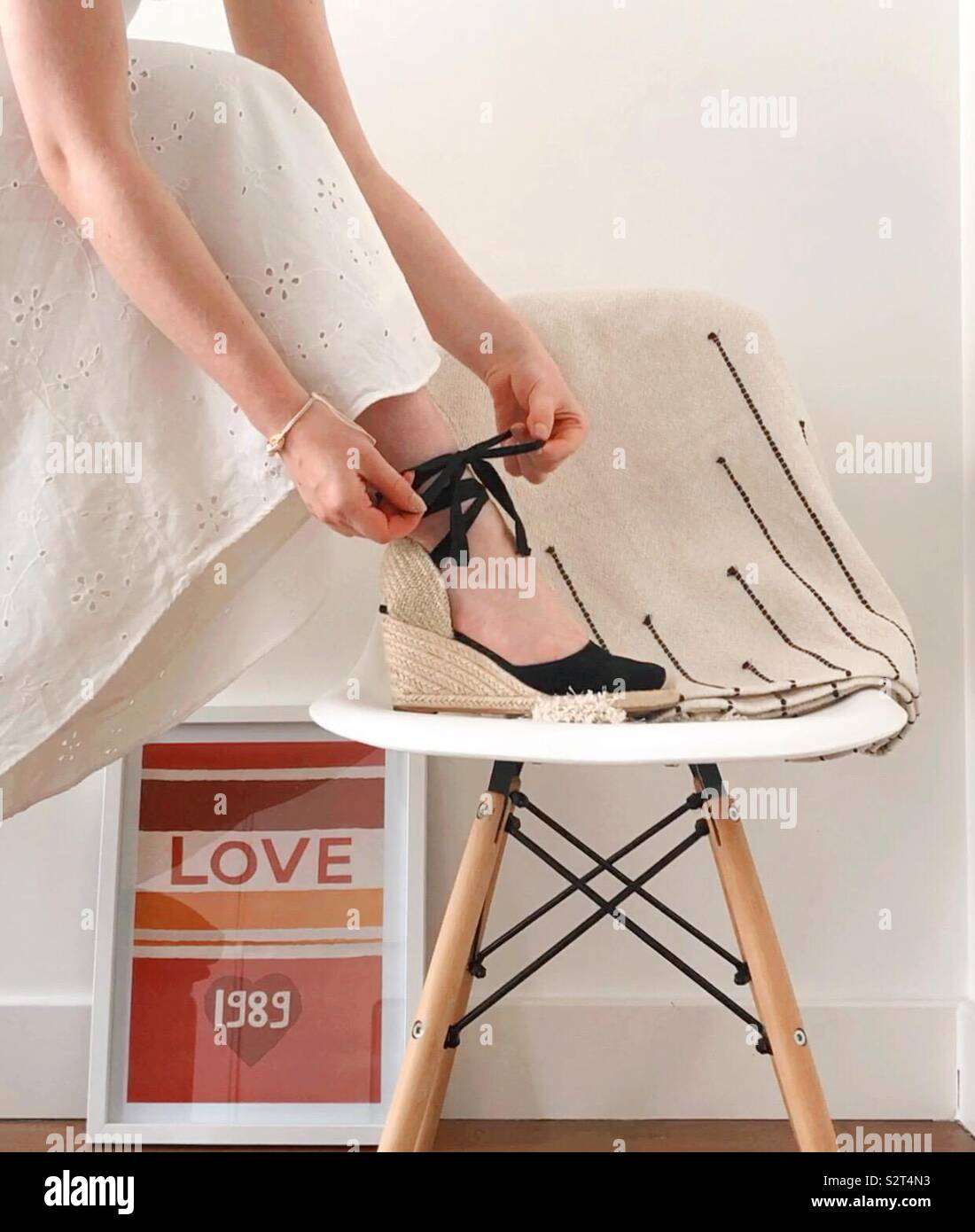 Woman in espadrilles heels standing on chair - Stock Image