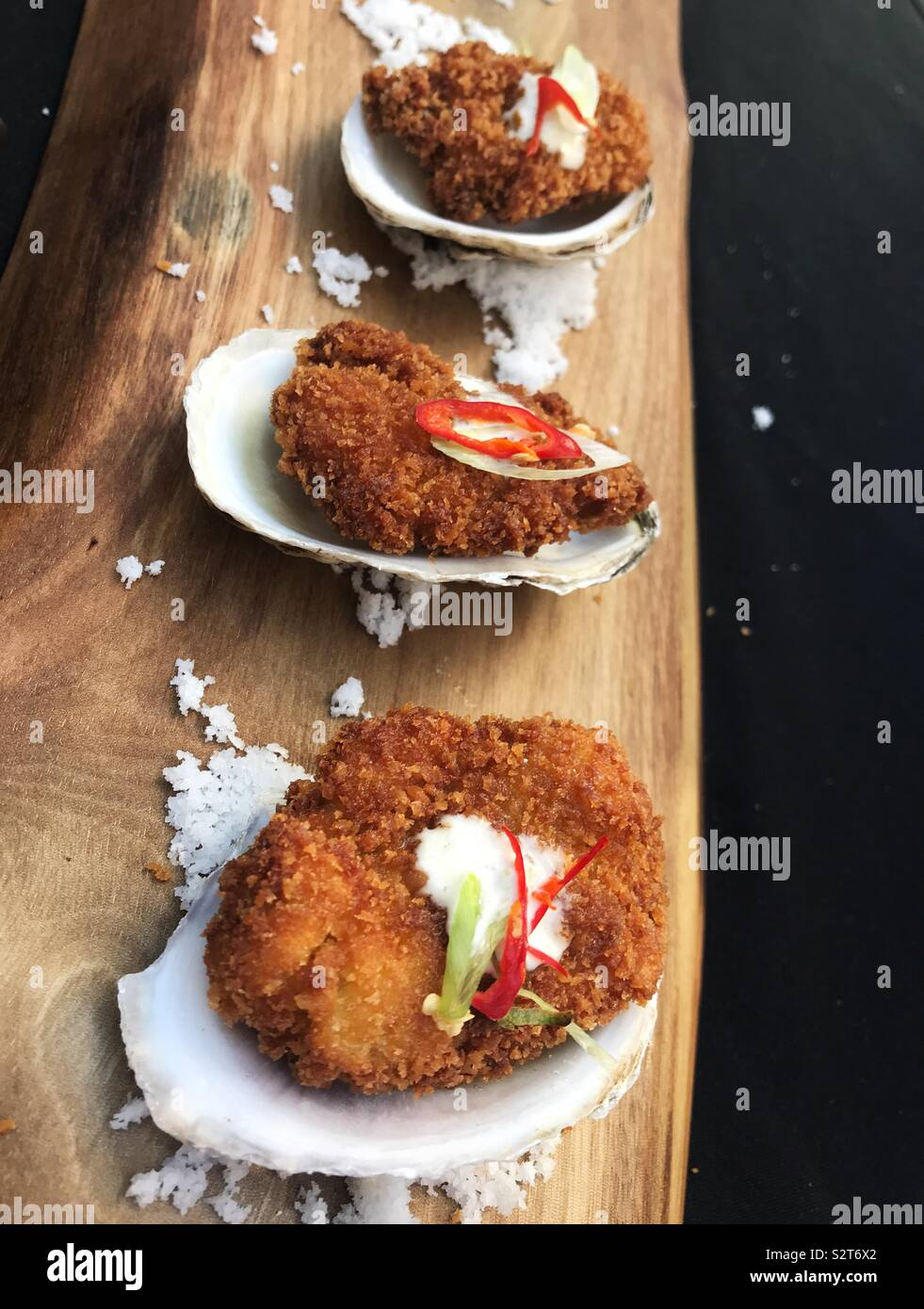 Fried oysters with aioli and jalapeño, served on the half-shell on a rustic wooden board, garnished with salt.  Elegant party food. - Stock Image