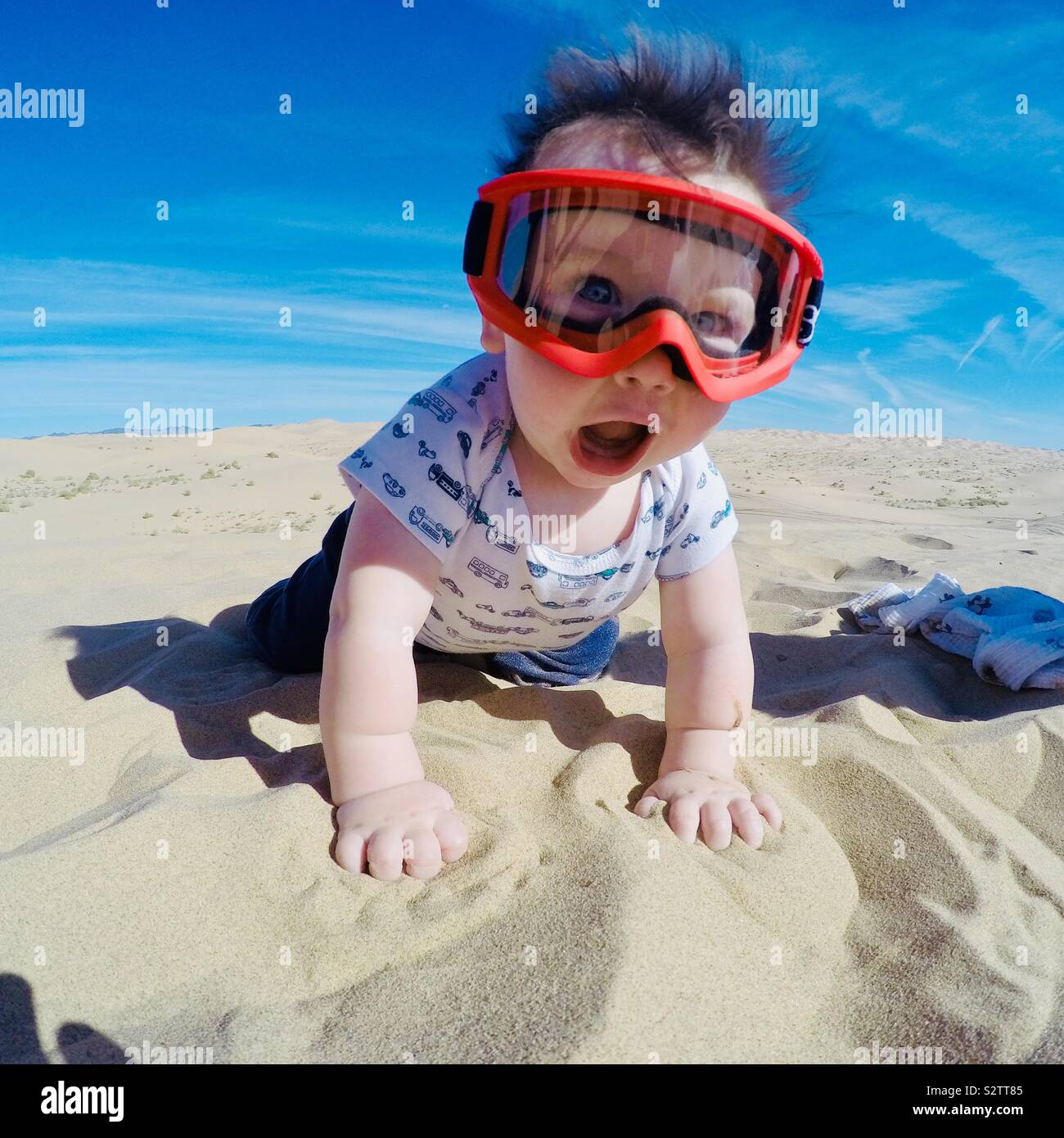 Baby playing in the sand wearing googles Stock Photo