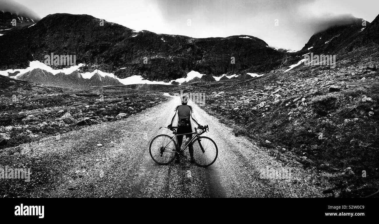 Female cyclist on gravel road, Romsdal, Norway Stock Photo