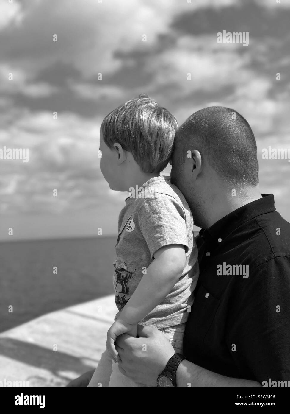Father and son looking at ocean Stock Photo