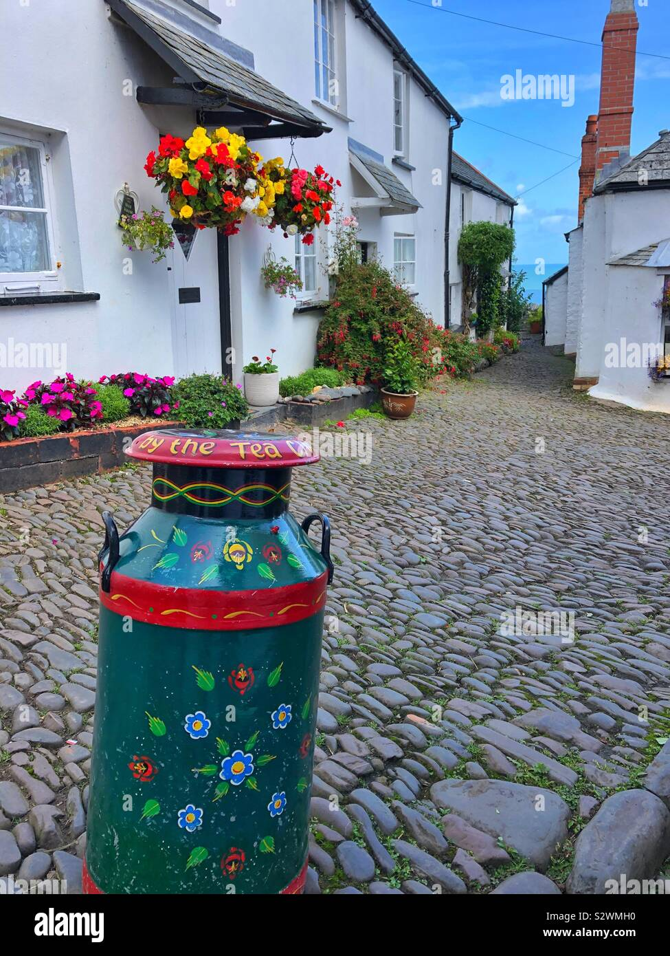 Decorated milk churn on the cobbled Street of Clovelly, North Devon. Stock Photo
