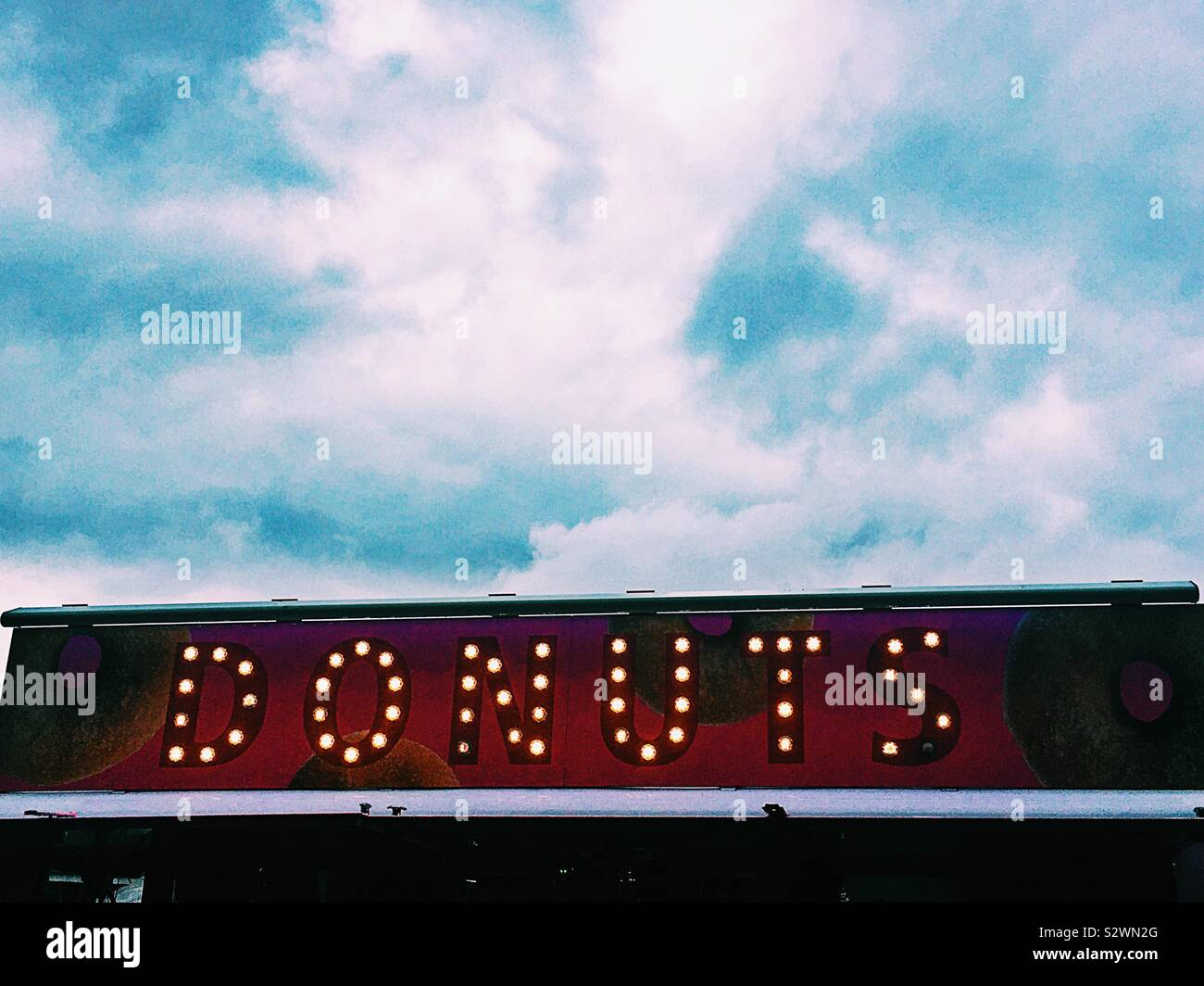 Donuts sign lights against blue cloudy sky Stock Photo