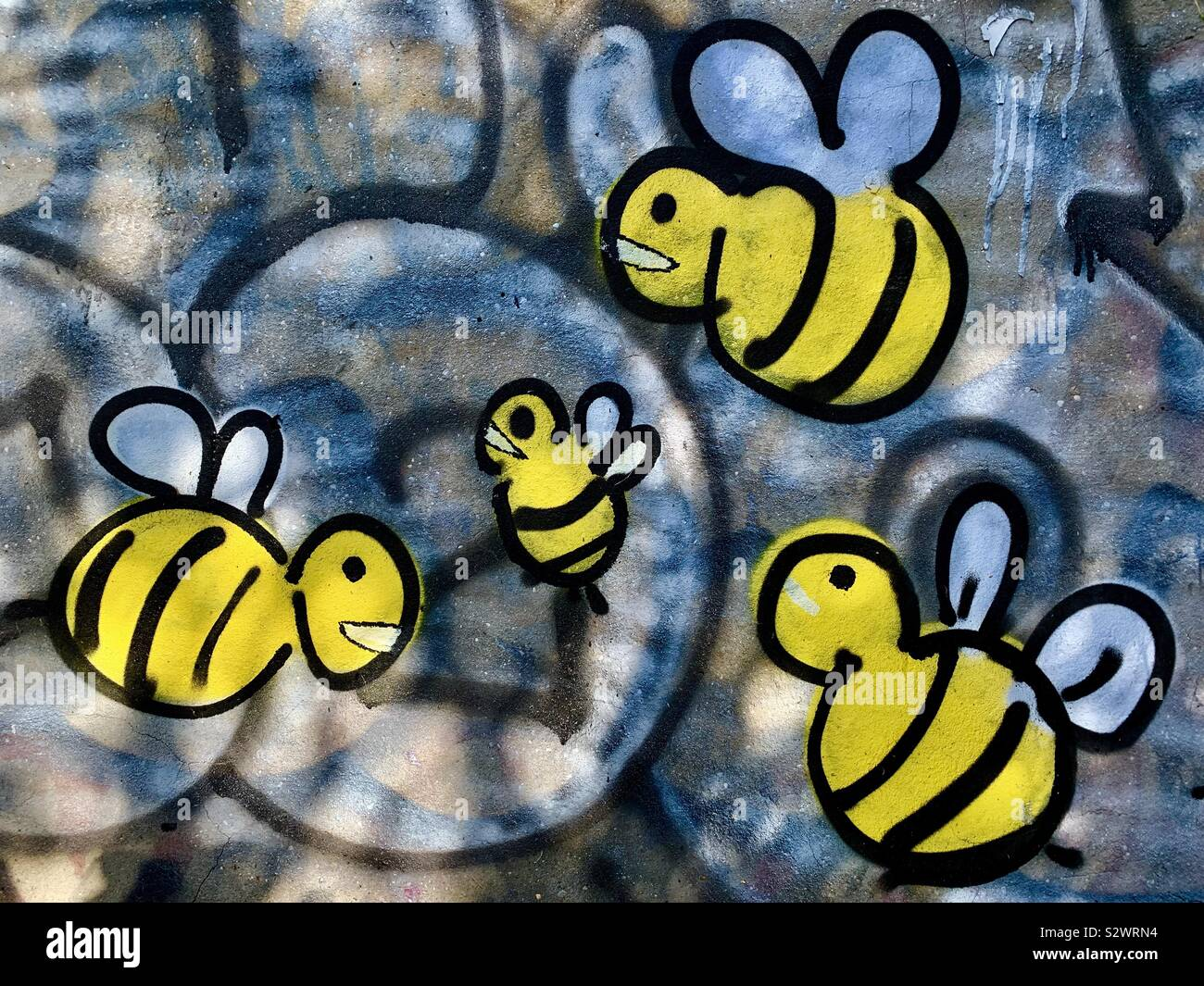 Graffiti of bees on a brick wall by Regent's Canal London. Stock Photo