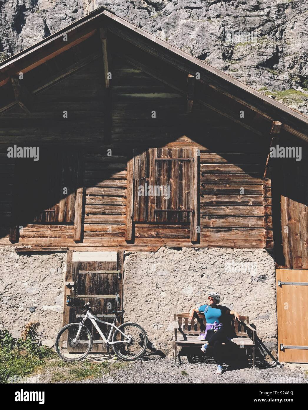 A girl with a bike sitting in front of a house in the mountain Stock Photo