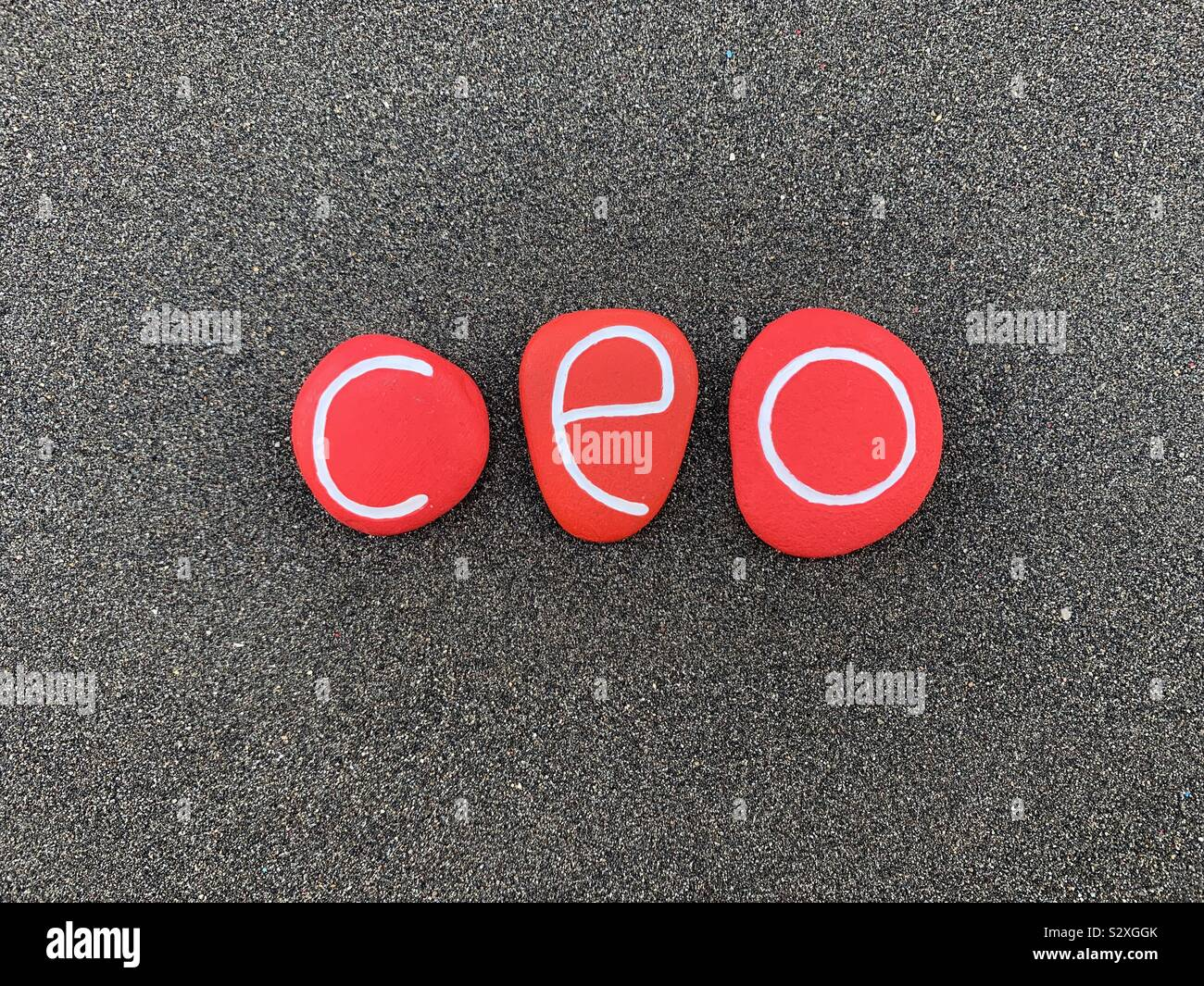 Ceo, Chief Executive Officer composed with red colored stones over black volcanic sand Stock Photo