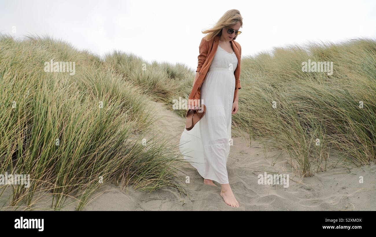 Young blonde woman in long white dress walking down sandy hill Stock Photo