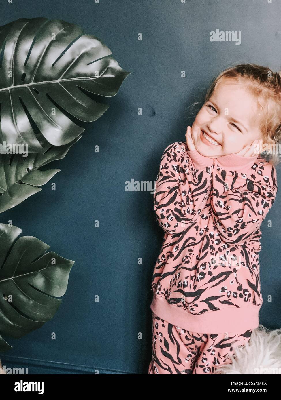 Three year old girl wearing pink animal print clothing Stock Photo