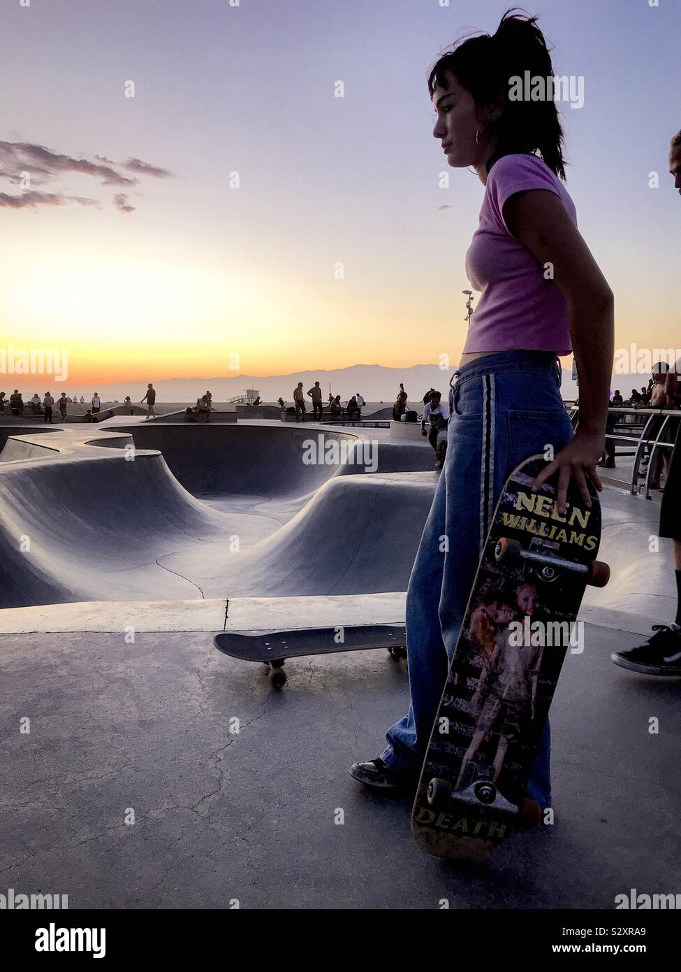 Skate girl contemplating the curves during golden hour in Venice CA. Stock Photo