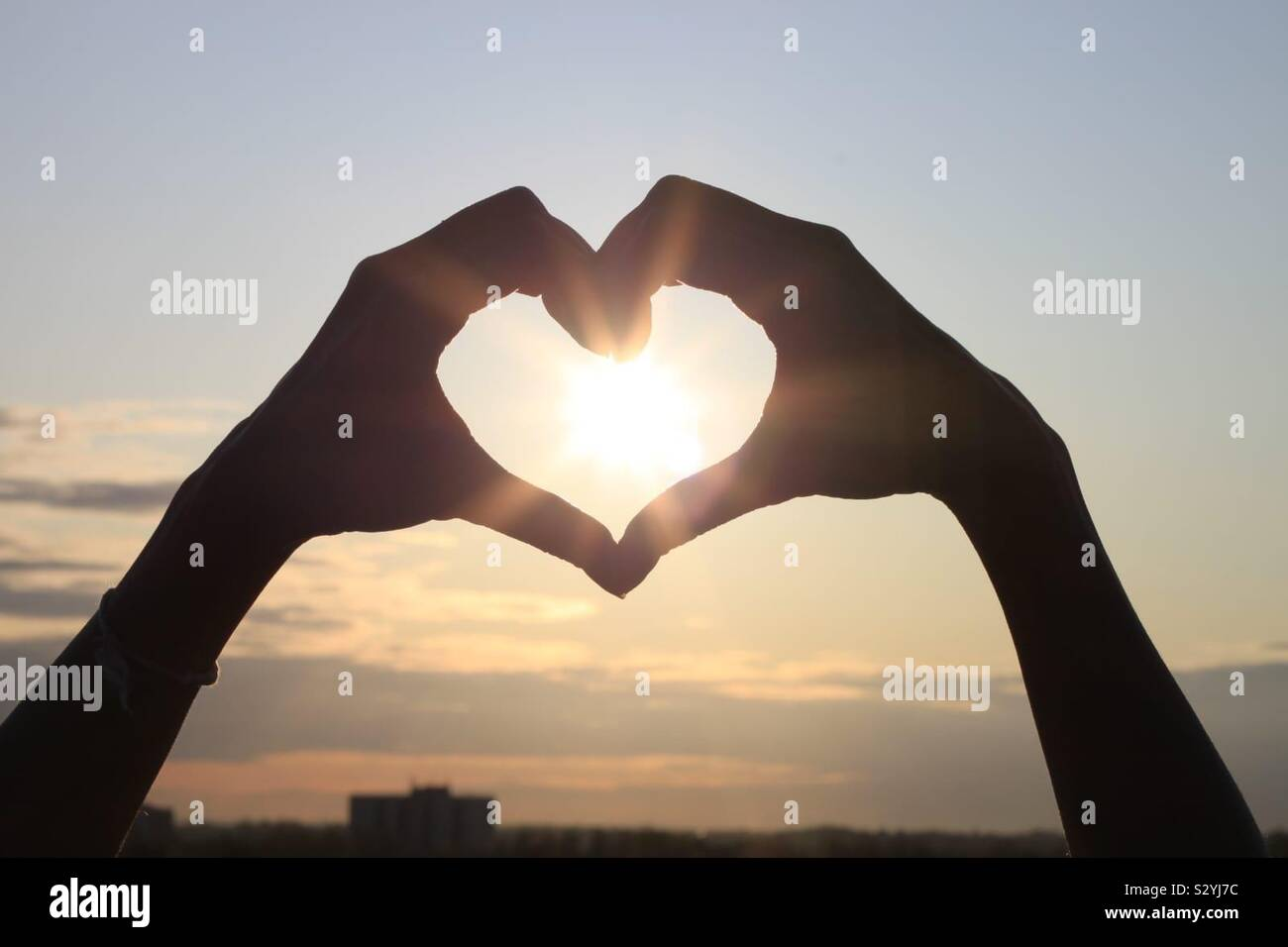 A persons hands forming a heart over the sun Stock Photo