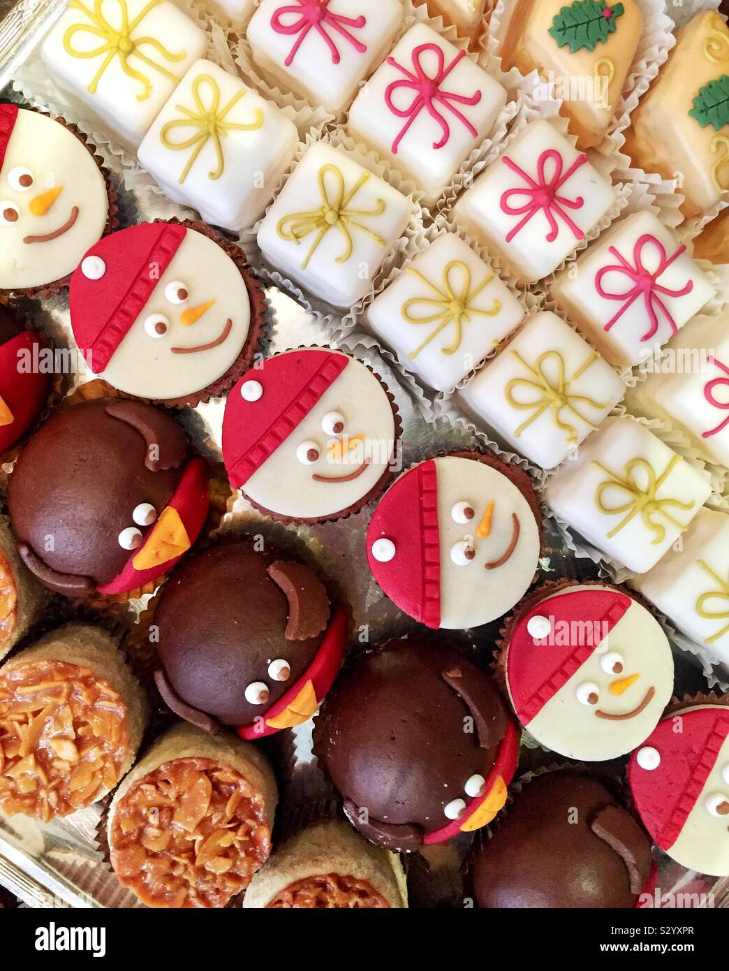 Looking down from above onto a variety of delicious cakes and fondant fancies in a French patisserie that are decorated with Christmas decorations and copy space Stock Photo