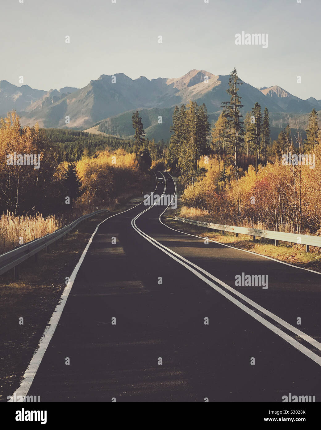 Autumn fall road landscape with view of the mountains. Stock Photo