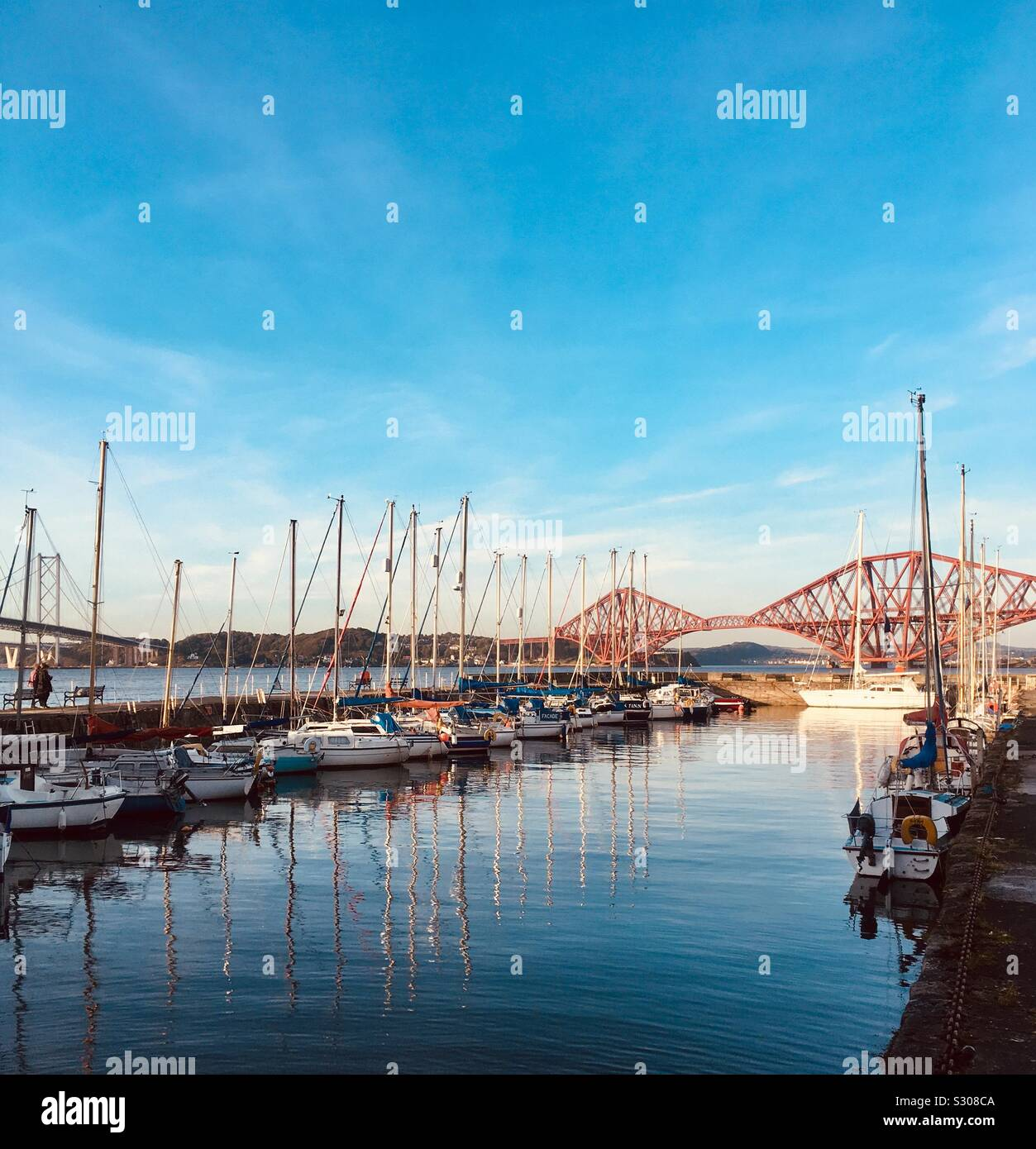 Fishing Boats in the harbour at Queensferry, watched over by the Forth Rail Bridge Stock Photo