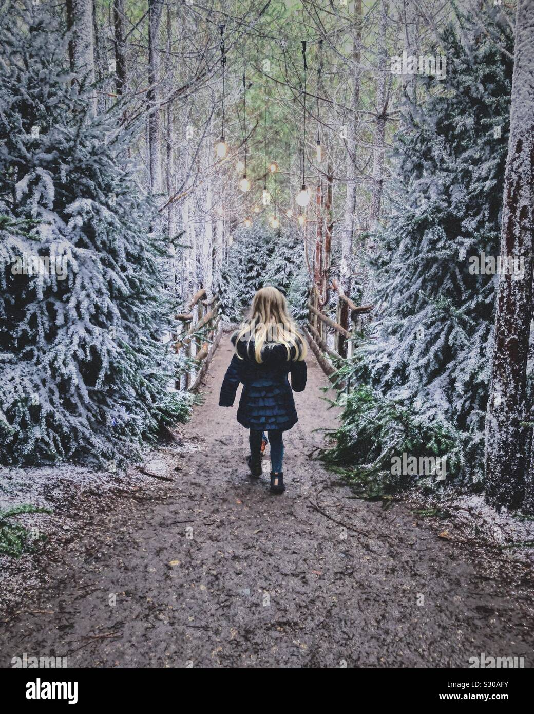 Little girl walking over snowy woodland bridge Stock Photo