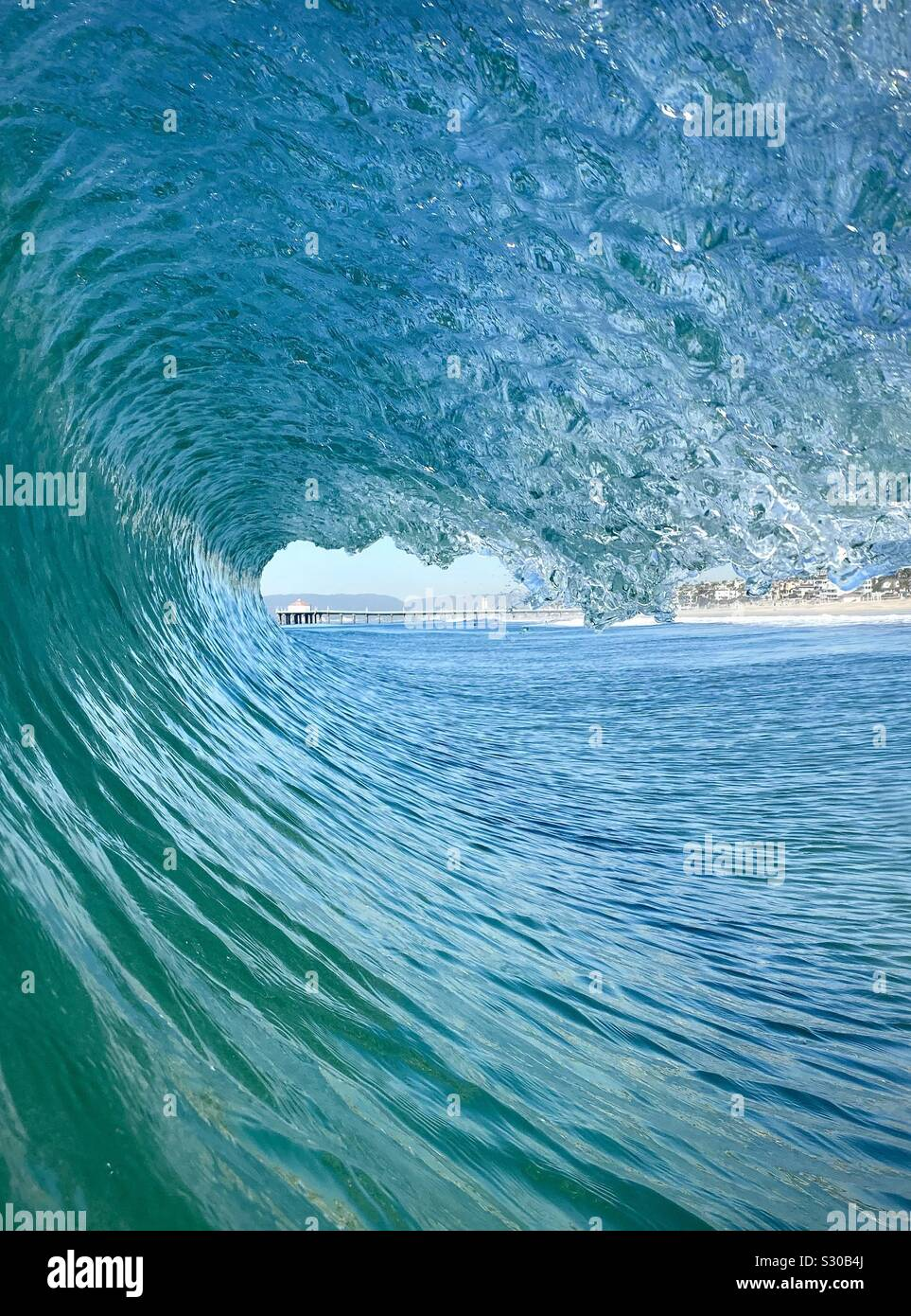 Inside, looking out of a barreling wave with Manhattan Beach pier in the background. Manhattan Beach, California USA Stock Photo