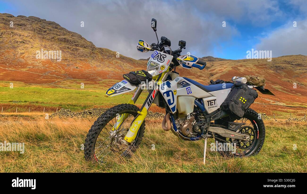 Husqvarna off road enduro motorcycle parked in wilderness of Lake District Cumbria Uk Stock Photo