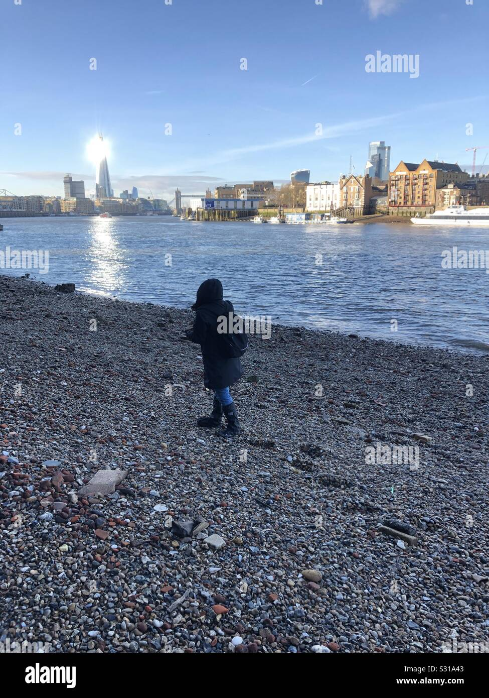 Woman walking on foreshore of River Thames near Rotherhithe London Stock Photo