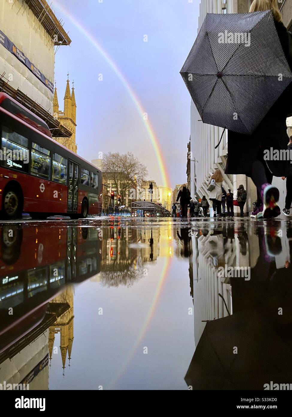 UK Weather: A rainbow shines over the Walkie Talkie building, as it is reflected on a rainy street in Holborn Viaduct, London, England. Stock Photo