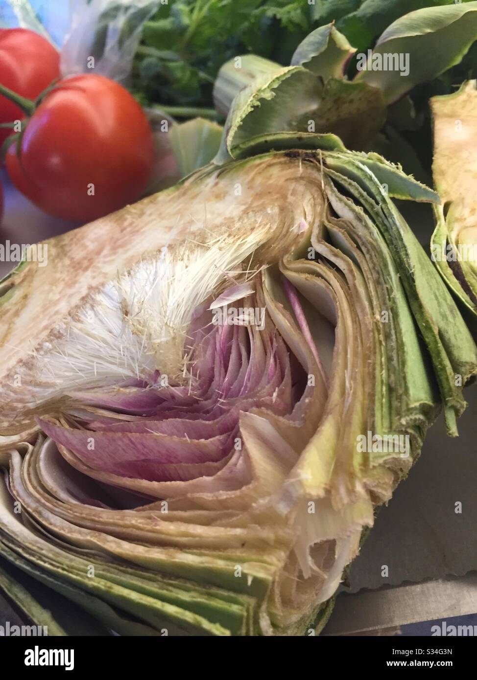 Still life of a cut in half artichoke and other vegetables on a cutting board in a residential kitchen, USA Stock Photo