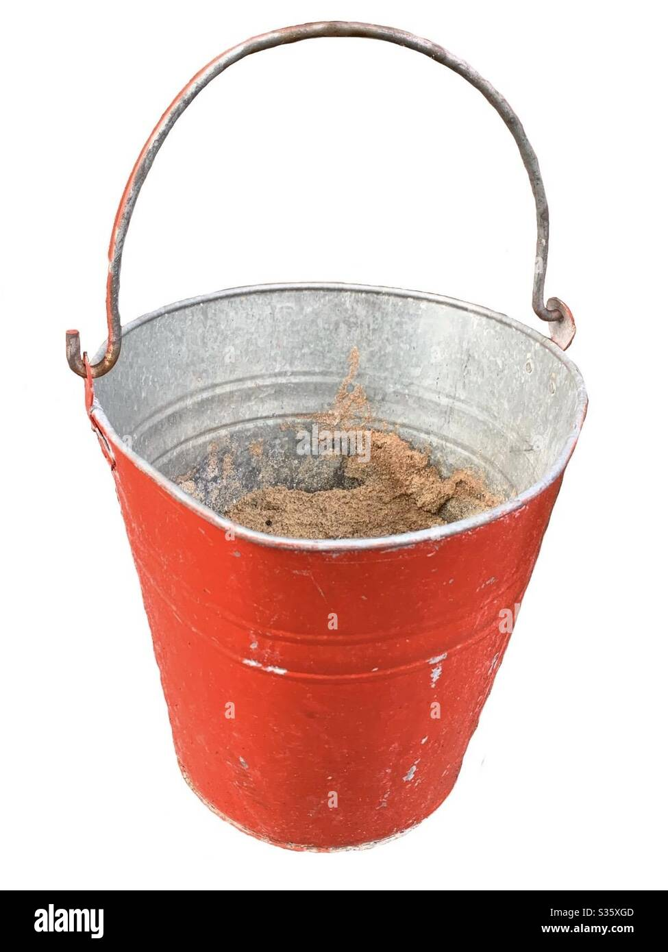 Red fire bucket with sand. Isolated background. Close up of a fire bucket Stock Photo