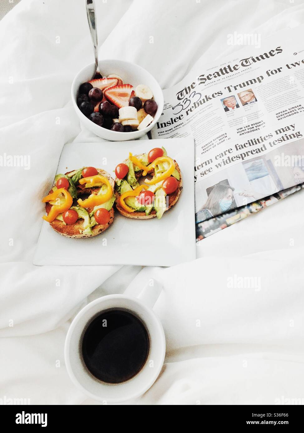 Newspaper, coffee and breakfast in bed Stock Photo