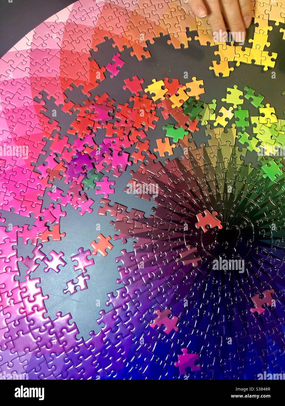 Completing a large colorful jigsaw puzzle Stock Photo