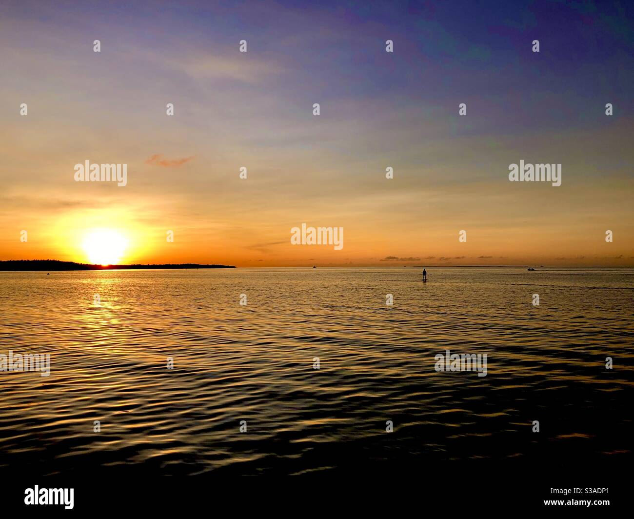 Serene and peaceful scene of a paddle boarder on the Bayside as the sun sets in Key Largo, Florida Stock Photo