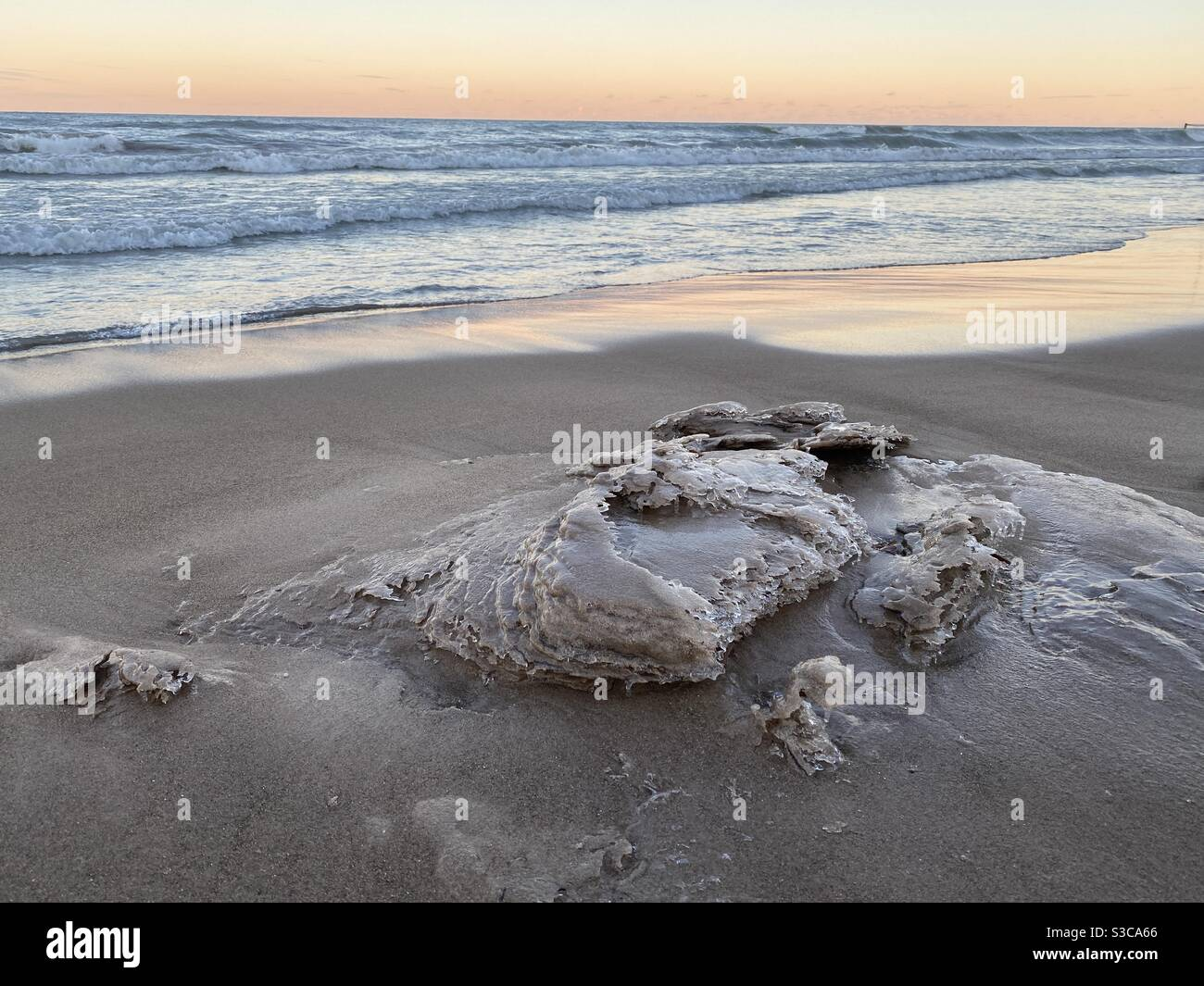 Winter waves leave icy sand sculptures on Lake Michigan beach. Sunset at Gillson Beach on the lake's Illinois shore. Stock Photo