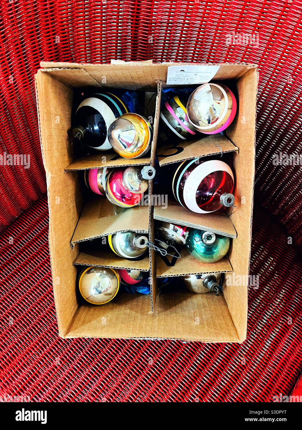 Vintage Christmas bubbles ornaments in and old cardboard box on red wicker chair Stock Photo
