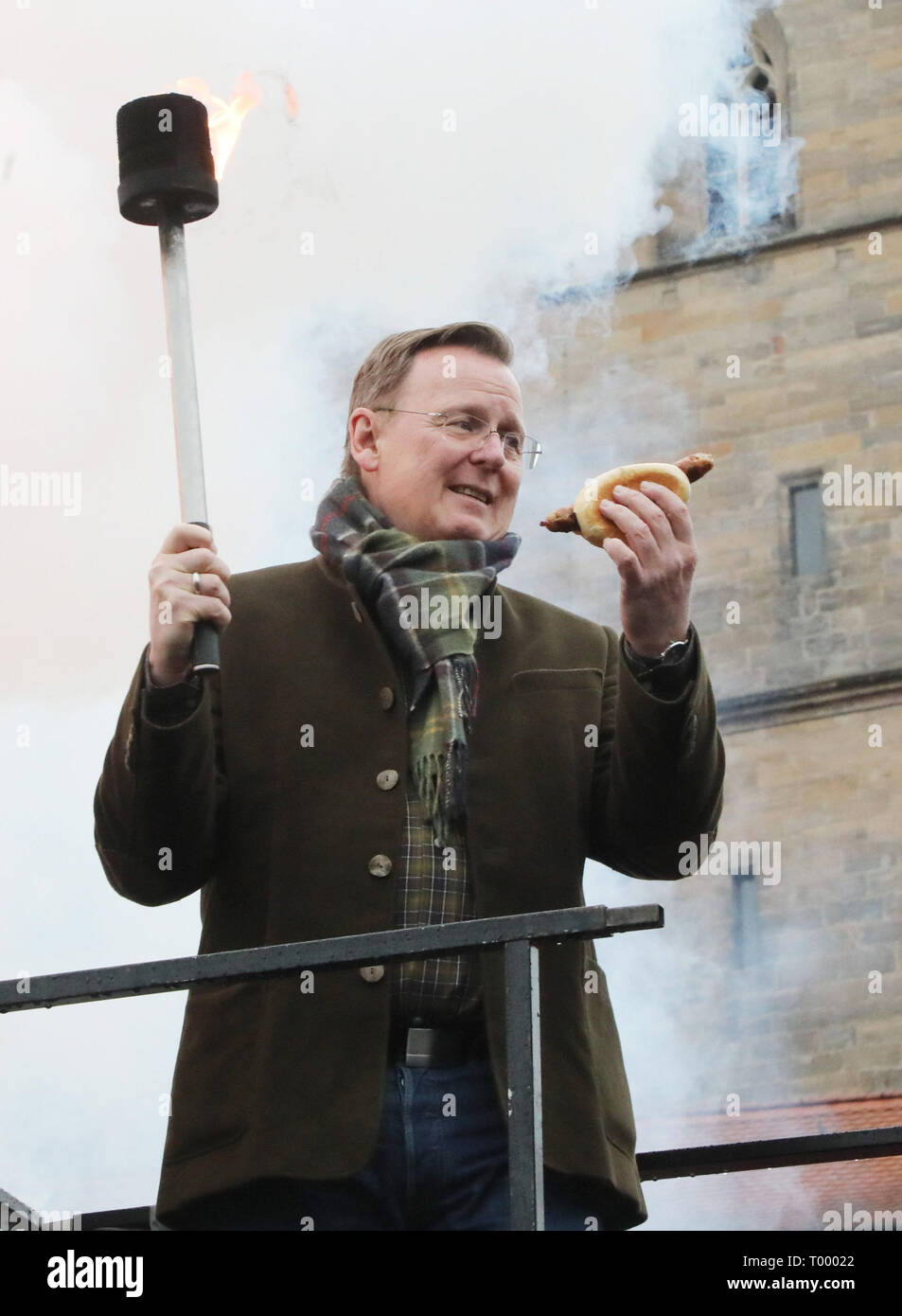 """Erfurt, Germany. 16th Mar, 2019. Thuringia's Prime Minister Bodo Ramelow (Die Linke) holds a grilled sausage and a torch in his hands at the opening of the barbecue season """"RostKultur - Thüringen glows up"""". 13 manufacturers of original Thuringian bratwursts present their sausages on the cathedral square. Credit: Bodo Schackow/dpa-Zentralbild/dpa/Alamy Live News Stock Photo"""