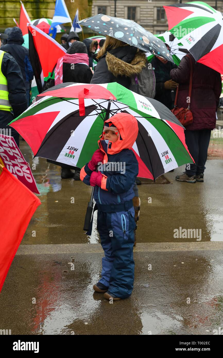 16th March 2019.16th March, 2019. George Square, Glasgow, Scotland, UK. A young girl shelters from the inclement weather under a Palestinian flag coloured umbrella at the 'Stand up to Racism' demo in Glasgow. - Stock Image
