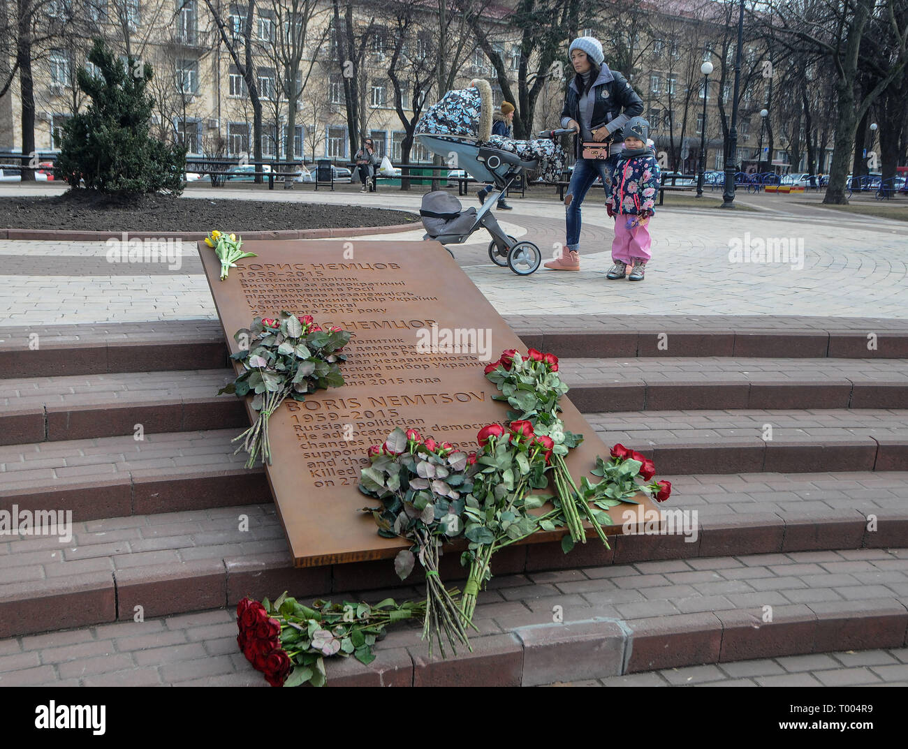 Kiev, Ukraine. 15th March 2019. A mother with her kids seen walking by the Boris Nemtsov plaque inside the square named after his name during the opening day. The Russian opposition leader Boris Nemtsov was killed 4 years ago in the center of Moscow on February 27, 2015. In the murder case, five Chechen natives were convicted and found guilty of the crime. Credit: SOPA Images Limited/Alamy Live News - Stock Image