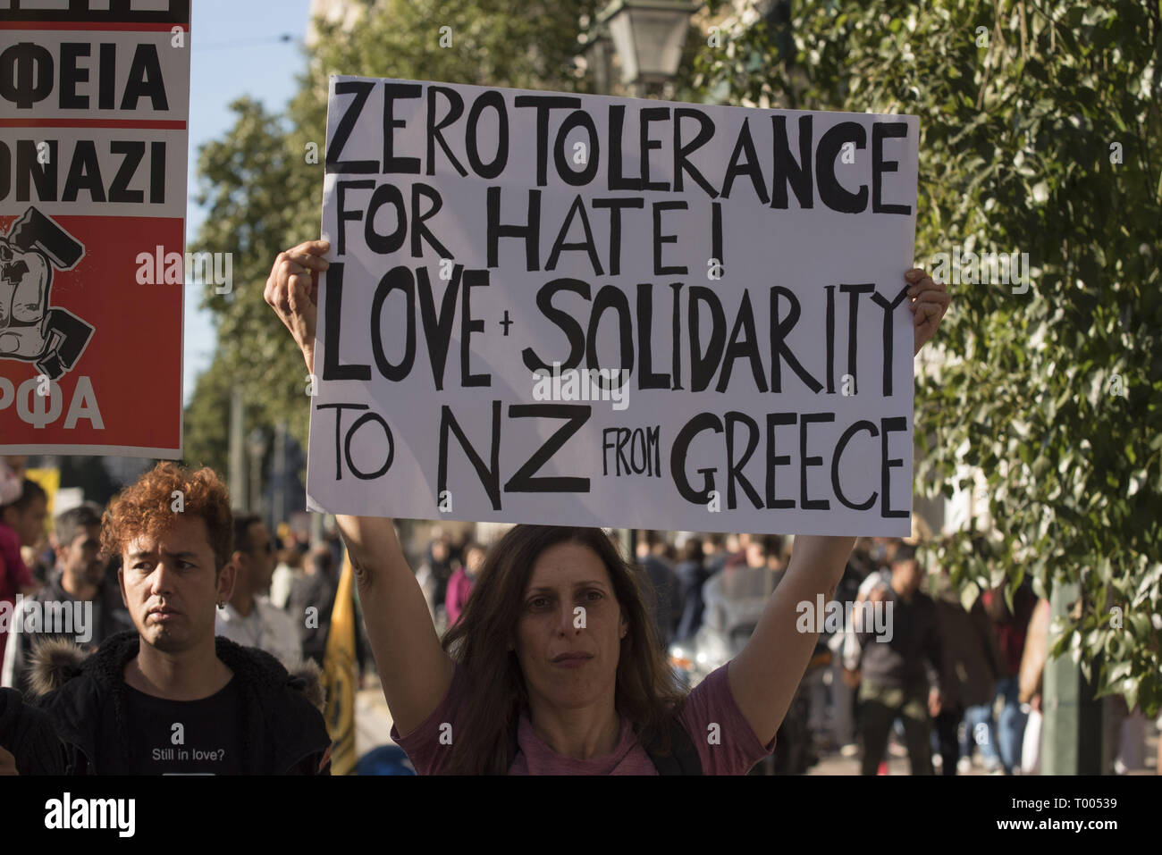 Athens, Greece. 16th Mar, 2019. A protester holds a placard with a message of solidarity to the victims of the racist attack in New Zealand. Leftist and anti-racist organizations staged a rally on the occasion of the International Day against racism to demonstrate against discrimination and racist policies and behaviours. Credit: Nikolas Georgiou/ZUMA Wire/Alamy Live News - Stock Image