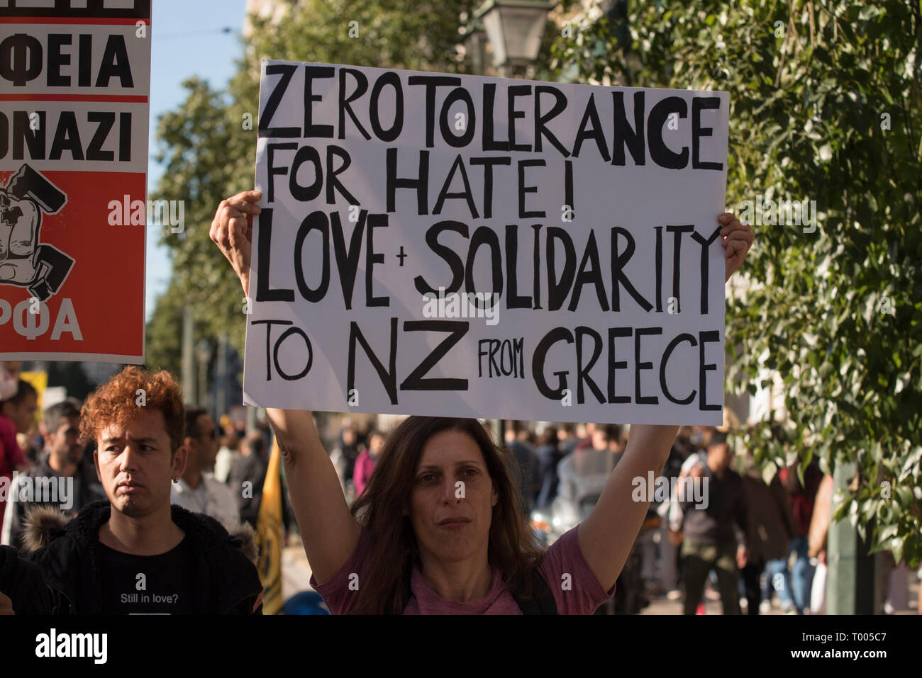Athens, Greece. 16th March 2019. A protester holds a placard with a message of solidarity to the victims of the racist attack in New Zealand. Leftist and anti-racist organizations staged a rally on the occasion of the International Day against racism to demonstrate against discrimination and racist policies and behaviours. © Nikolas Georgiou / Alamy Live News - Stock Image