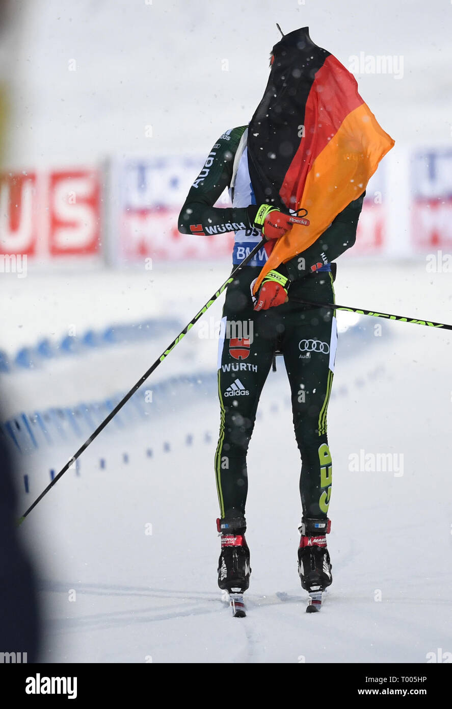Östersund, Sweden. 16th March 2019. World Championship, relay 4 x 7, 5 km, men. Benedikt Doll from Germany cheers and finishes second with the German flag. Credit: dpa picture alliance/Alamy Live News Credit: dpa picture alliance/Alamy Live News - Stock Image