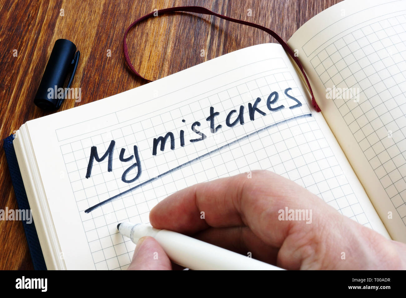 Man is writing My mistakes in a note. Inner critic concept. - Stock Image