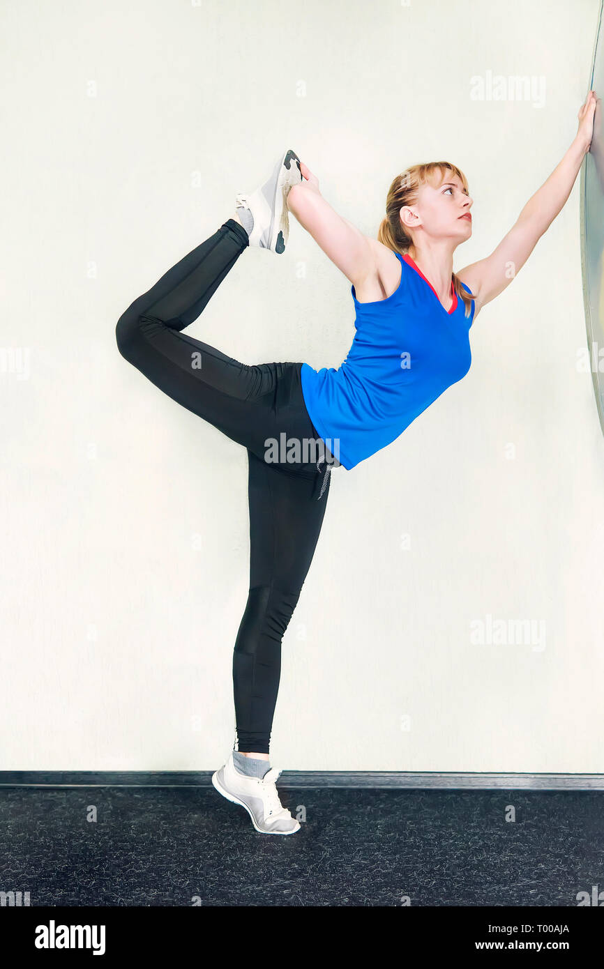Young blonde woman doing a yoga pose standing on one leg and stretching near a white wall. Utthita Hasta Padangusthasana. - Stock Image